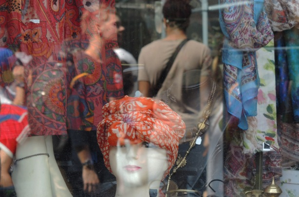 a head mannequin in a store window, with an orange piece of fabric wrapped aroungd her head. Other fabric in the window. also two people reflected in the glass
