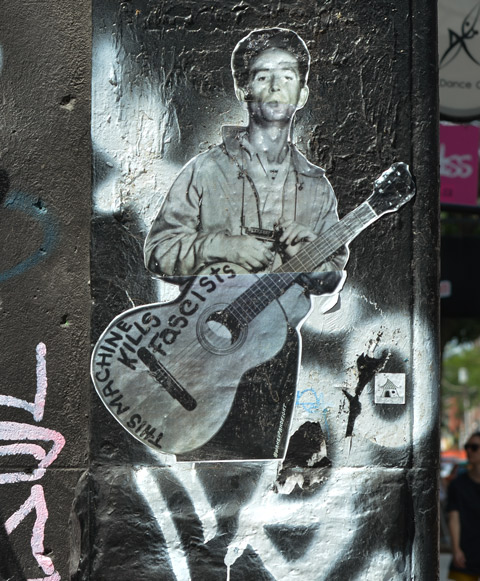black and white paste up of Woody Guthrie standing, holding onto his guitar that has the words This machine kills fascists, written on it.