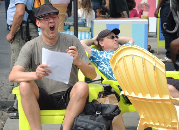 two men with baseball caps are sitting on yellow Muskoka chairs on a sunny afternoon. One is facing the camer - he is holding a piece of paper in one hand, he is yawning.