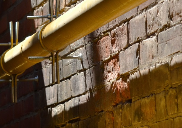 along an old brick exterior wall, there are two yellow gasline pipes that are held onto the wall with clamps