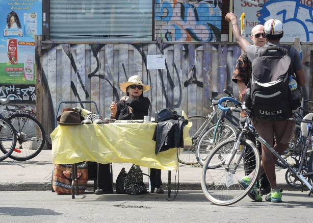 Two men stand beside their bikes talking, a woman in a straw hat an dsunglasses sits behind a table with a yellow table cloth with items for sale on the table