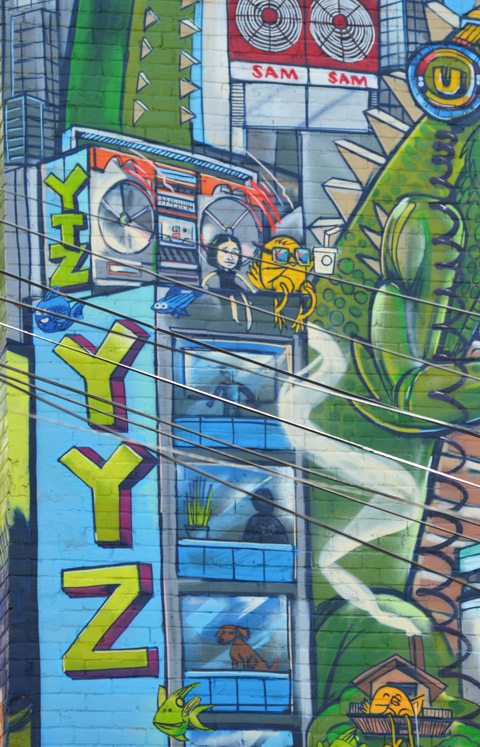 part of an Uber 5000 mural, yyz, condo building with balconies, a woman sitting on the roof with a yellow birdie, ghetto blaster on the roof, Sam the Record man sign,