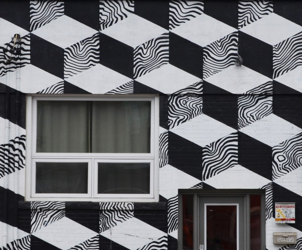 the front exterior wall of a building is decorated with a painting of 3D cubes arranged in an optical illusion