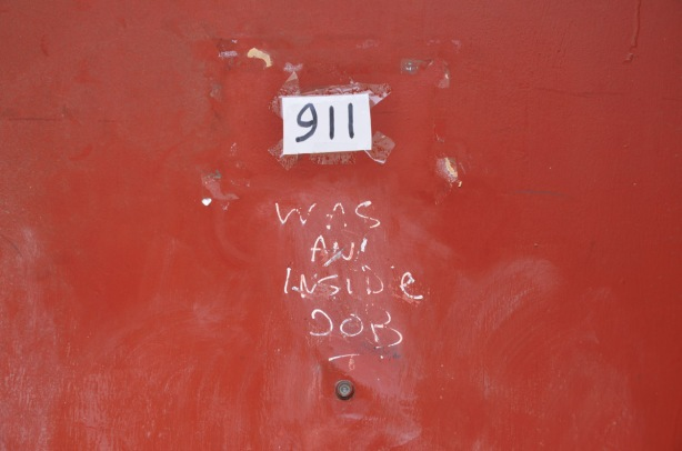 on a red door, number 911, someone has added in white letters, was an inside job