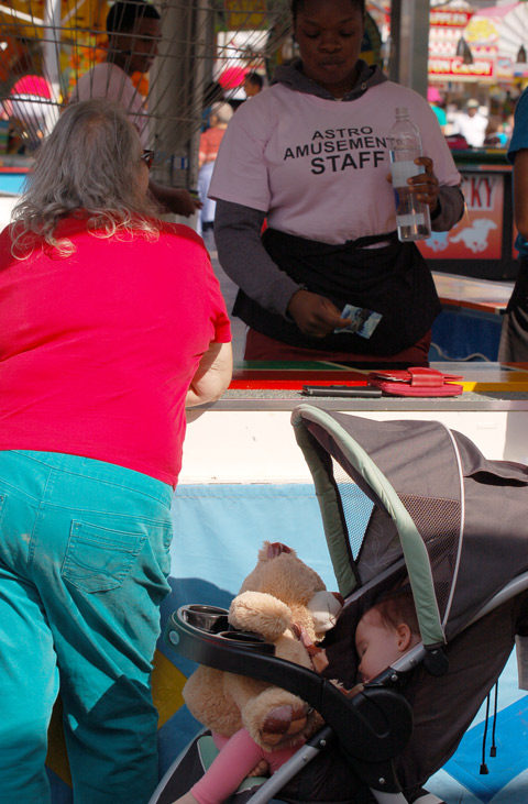 a baby is asleep in a stroller while the adult bets at a game of chance at the Ex. The baby has a large stuffed brown bear