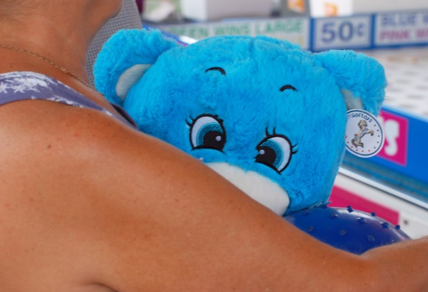 the eyes of a large blue stuffed bear peaking from behind a woman's arm