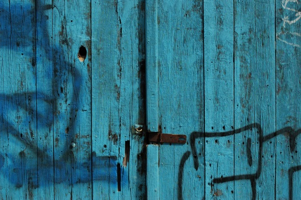 part of an old wood door that is part dark turquoise and part blue, with a rusted latch holding the two doors together and closed