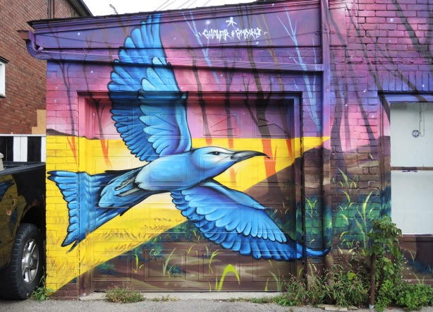 part of a larger mural by Clandestinos (Shalak Attack and Bruno Smoky) on the side of Riders bike store, a bluebird in flight painted on the garage door, yellow triangle of light behind it