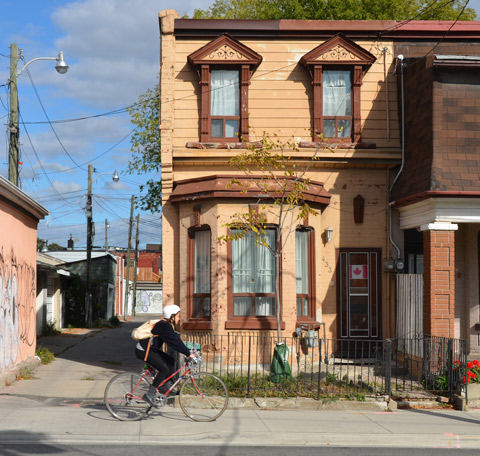 a girl on a bike rides past the entrance to an alley. Behind her is a two storey house in tan coloured siding, with darker tan trim, bay window, Canadian flad in the doorway,