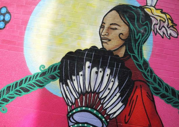 detail of center of mural of an indigenous woman with long braided hair and feathers
