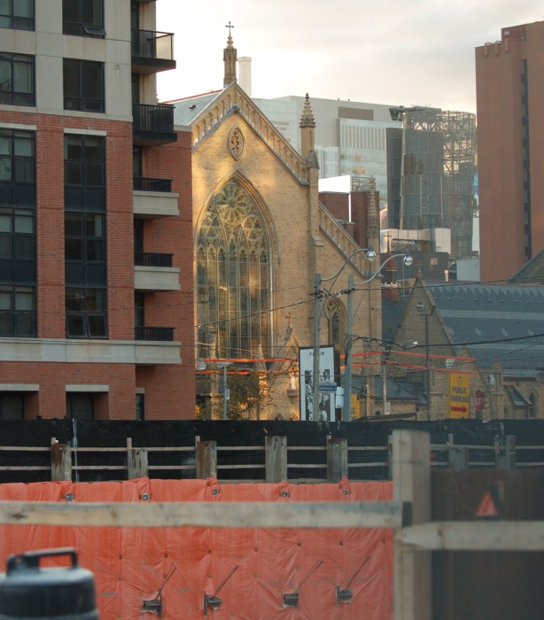 one end of St. Michaels Cathedral with reflected light falling on it, new buildings and construction surround it