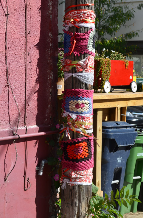 a utility pole is wrapped in crocheted squares in many colours, the house beside the pole is bright pink