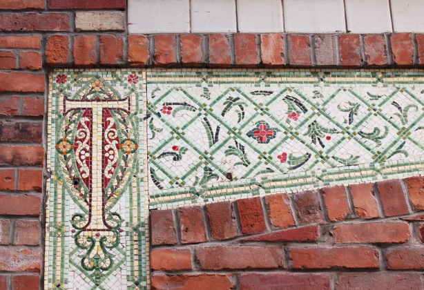 decorative tiles form a panel on the front of a brick building, red flowers, green lattice and an elaborately embellished letter t