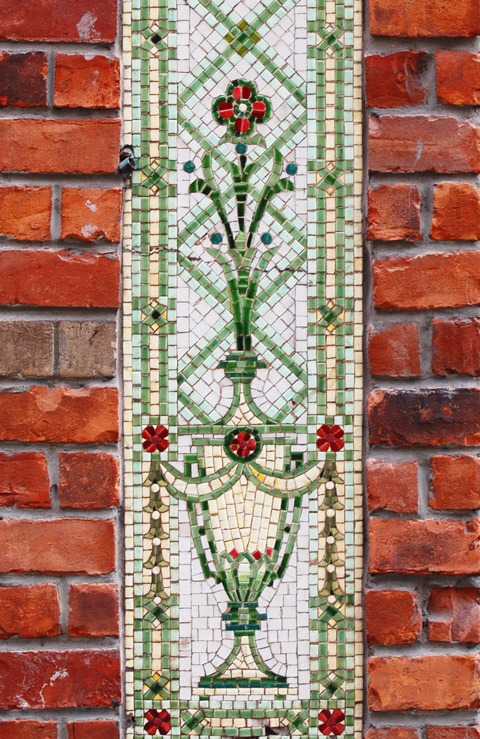 decorative tiles form a panel on the front of a brick building, red flowers, green lattice,