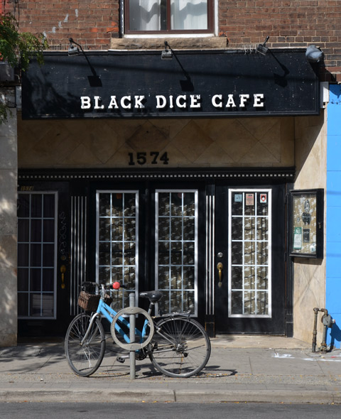 a blue bike is parked outside the glass windows and door of the black dice cafe