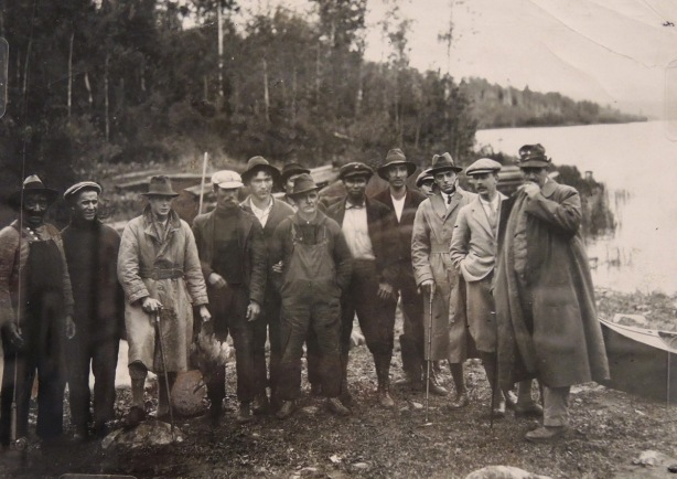 a vintage black and white photo of a group of men in northern Ontario, by a lake, one is holding a duck that has been shot