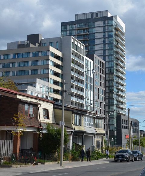 In the background, two large high rise buildings, modern, in the foreground, a row of older two storey houses