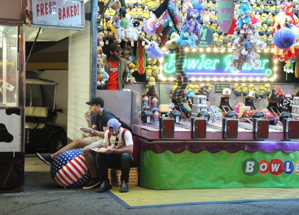 two young men sit on stools beside a midway game at the ex while they eat