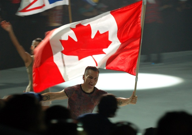 Elvis Stoyko carries a Canadian flag at the end of the ice skating show at the Ex, some of the crowds in the seats can be seen in front of him