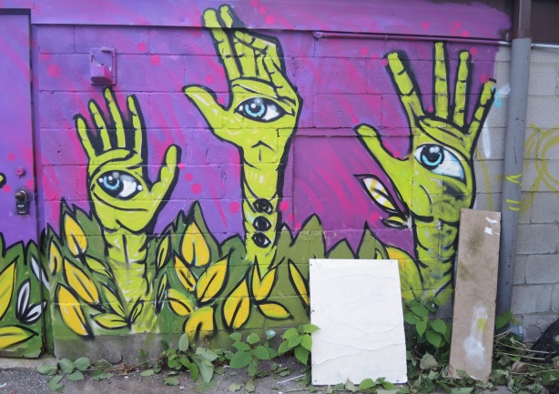 part of a mural with magenta background, green arms reaching up from foliage and weeds at the bottom, hands open, revealing a large blue eye on each hand