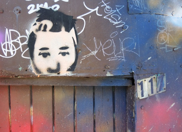 paste up of a man's face over a wood door, door and wall have blue and red splotchy spray paint on them