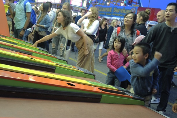 a young boy throws a ball ina Skee Ball game while his sister and parents watch