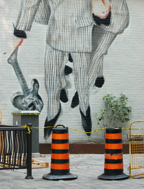 bottom part of mural, guitar player and band dressed in white suits with black stripes, black pointy toe shoes, wall is behind two orange and black cones.