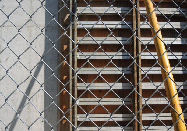 chainlink fence in front of rows of construction equipment