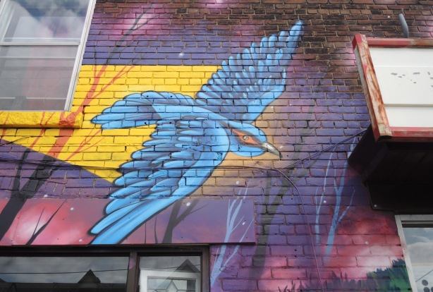 part of a larger mural by Clandestinos (Shalak Attack and Bruno Smoky) on the side of Riders bike store, a blue bird in flight with purplish coloured sky behind