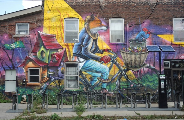 part of a larger mural by Clandestinos (Shalak Attack and Bruno Smoky) on the side of Riders bike store, main part of mural, a fox in jeans is riding a bike with a wicker basket in the front