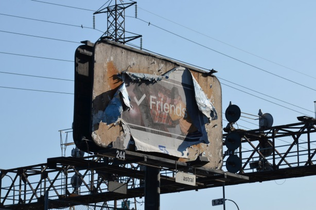 large billboard close to lights across the railway tracks, picture is badly peeling away from the edges. The picture in the middle is faded, but the word friend is written on top of it.