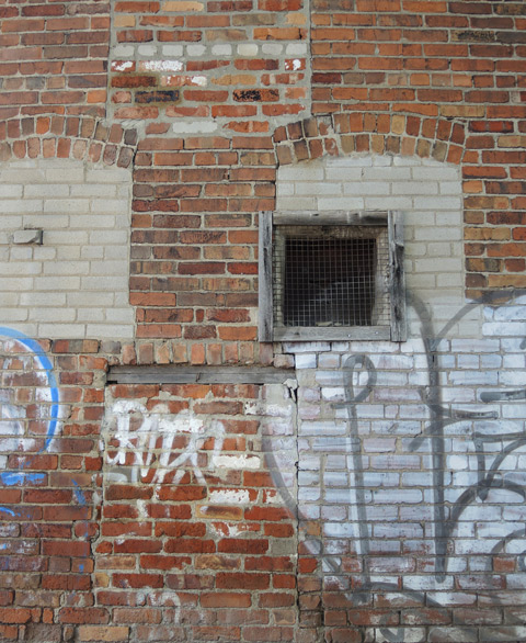 part of a brick wall that has old windows bricked over in a different brick, an old window with old wood frame, unpainted, some graffiti on the wall