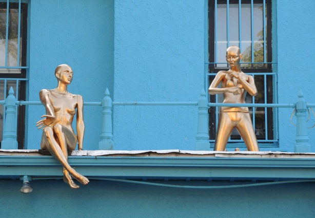 two gold coloured mannequins with no clothes on are on a balcony of a blue building. one is sitting on the edge and one is standing