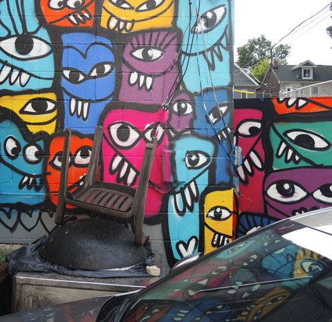 small street art mural of many stylized abstract goofy faces in bright colours, on a wall.  a car is parked in front of it and some is reflected in the windshield
