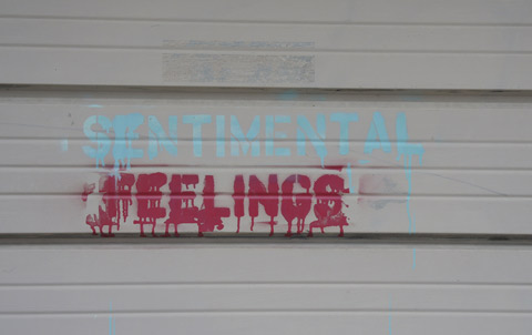 graffiti words stenciled on a garage door that say sentimental feelings.