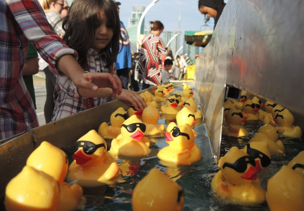 reaching for a yellow rubber ducky with black glasses and bright red lips, ducks are floating in water, a game of luck on the midway at the CNE