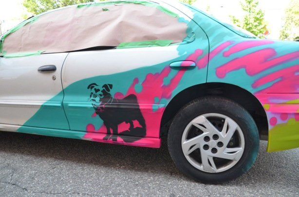 side of a car that has been prepped, for painting partially painted with turquoise section and pink splotches, also a black stenciled dog, called Harley, by the back wheel,