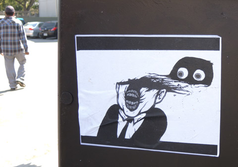 pasteup in black and white of a man with open mouth, his eyes are attached to a black baseball cap that is blowing off his head, to the side and back from his head. he's wearing a black suit and tie.