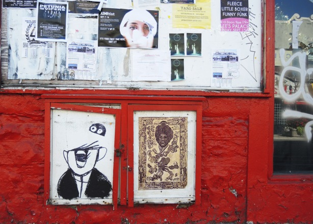 two paste ups on a red wall