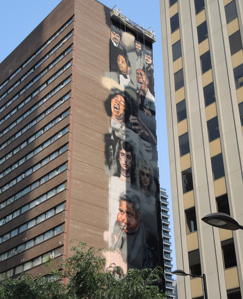 tall mural, 22 storeys tall, on the side of a TCHC apartment building in Toronto, by Adrian Hayles, portraits of Canadian musicians such as the band Rush, Carole Pope and others