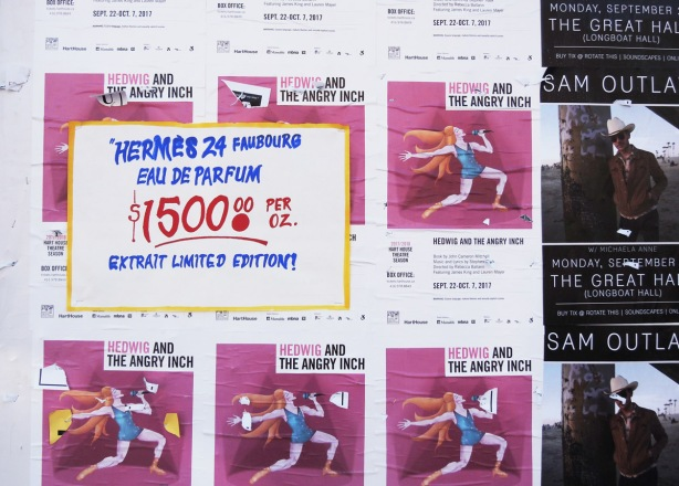 advertising posters and graffiti on a wall, graffiti is a mock ad for perfume at $1500