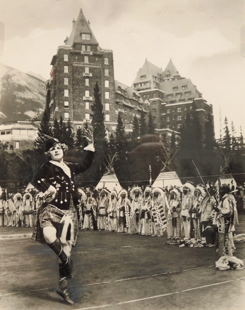 vintage black and white photo of a highland dancer with a line of native Americans in traditional dress behind her. Some teepees in the background, also a hotel.