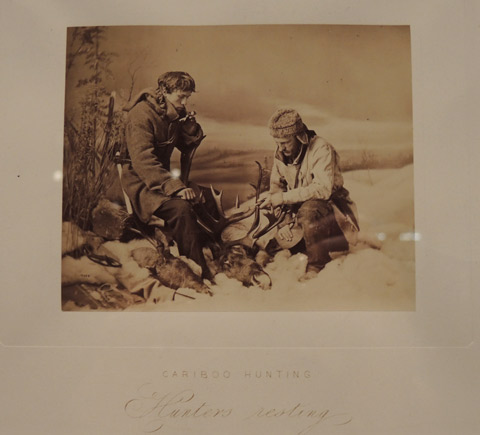 vintage photo of two men hunting caribou. Resting with their rifles.