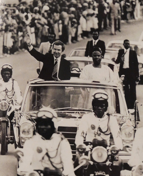 black and white photo from 1979 of Joe Clark, then Prime Minister of Canada, riding in a motorcade with the President of Cameroon, in Cameroon.