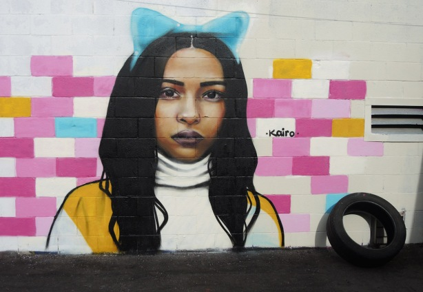 portrait of a woman on a wall, a mural by kairo, long dark hair, a blue bow on the top of her head, some blocks of the concrete block wall are painted in shades of pink