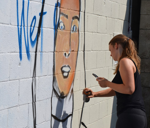 a woman is in the beginning stages of painting a mural portrait of a woman outside