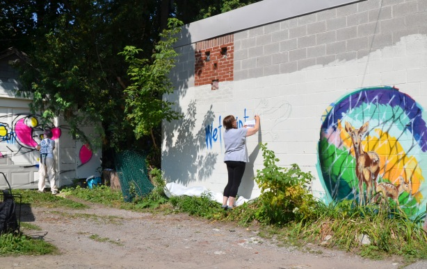 two women painting murals, Kim is in the background painting on a garage door while another woman is outlining a picture of a chameleon on a wall