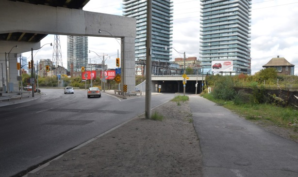 intersection of lakeshore blvd and cherry street from the southeast, cherry street bridge for the tracks, 3 condos of the distillery district, some traffic, billboards, concrete