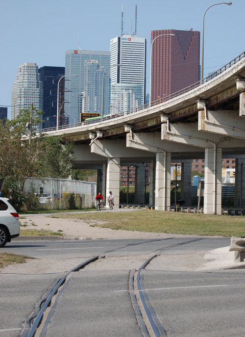 looking west along the Gardiner Expressway and Lakeshore Rd, curve of the Gardiner as it passes over the bottom of Cherry Street, downtown skyline with CN tower, cyclists on the bike path on the south side of Lakeshore