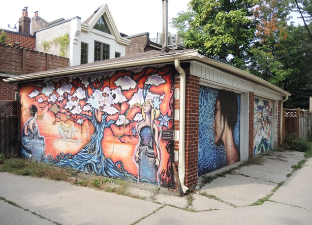 a two car garage in an alley, murals on both garage doors as well as on the side of the building